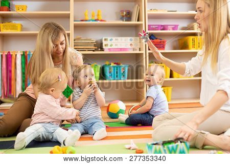 Group Of Babies In Nursery. Nursery Teacher And Assistant Play With Kids On Cosy Rug