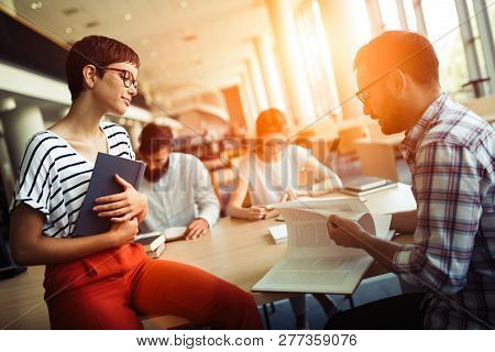Group Of College Students Working Together In The School
