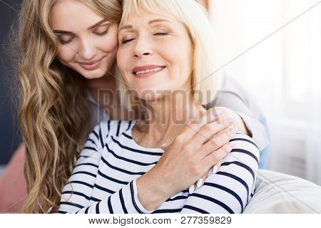 Cute Young Daughter Embracing Her Mother With Love, Sitting On Sofa At Home