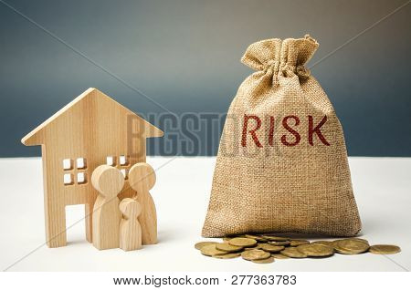 A Money Bag With The Word Risk And A Family Standing Near The House. The Concept Of Risk, Loss Of Re