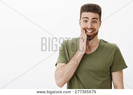 Indoor shot of surprised happy and excited good-looking man being kissed in cheek feleing thrilled and upbeat touching face with palm raising eyebrows and smiling from happiness over white wall poster