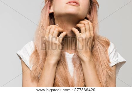 Isolated studio portrait of young beautiful woman in white t-shirt scratching neck with both hands/irritation, sensitive skin, allergy symptoms, rhinitis, cold, itch, healthcare and medicine concept.