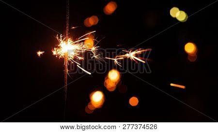 New year party burning sparkler closeup on unsharp dark background. sparkling hand fireworks
