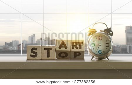Wooden Blocks With The Word Start-stop And Clock On Table With Panoramic City Skyline Background In