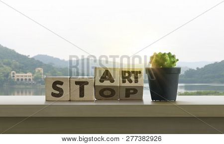 Wooden Blocks With The Word Start-stop And Cactus On Table With Panoramic Lake Landscape Background