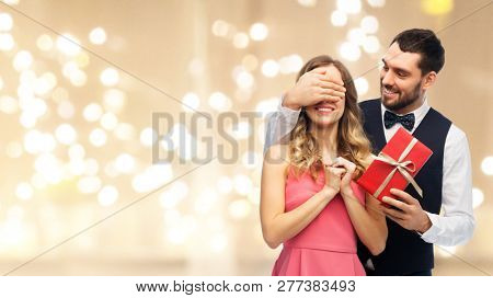 valentines day, couple, relationships and people concept - happy man giving woman surprise present over beige background with festive lights