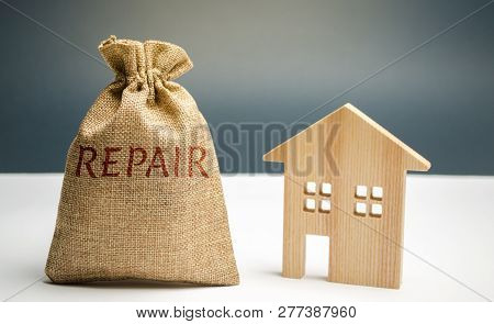 Money Bag With The Word Repair And A Wooden House. Saving And Accumulation Of Money To Repair. Conce