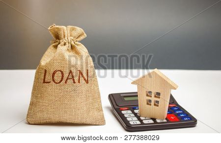 Money Bag With The Word Loan And A House On The Calculator. Loan Calculating. Interest Rates Calcula