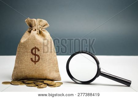 Money Bag With Dollar Sign And Magnifying Glass. The Concept Of Finding Sources Of Investment And Sp