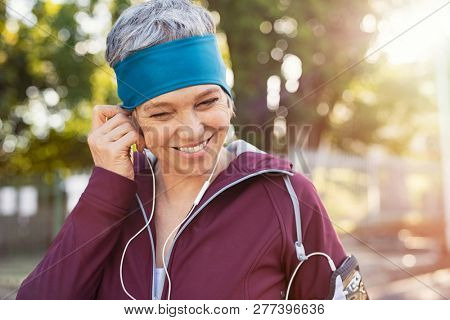 Portrait of smiling senior woman listening to music after running. Healthy mature woman wearing blue headband and sportswear adjusting earphones. Closeup face of retired woman jogging at park.