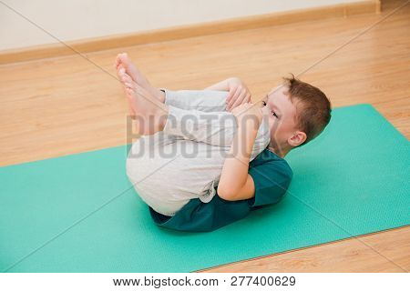 Cute Little Boy Is Learning To Do Yoga In The Gym