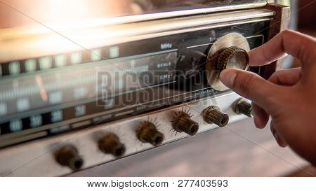 Male Hand Turning Retro Radio Button. Listen To Music Or News With Old Classic Radio Receiver. Vinta