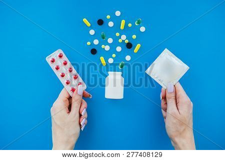 Birth Control Pills And An Unwrapped Condom. Colored Pills And Capsule On Blue Background. Pharmacy