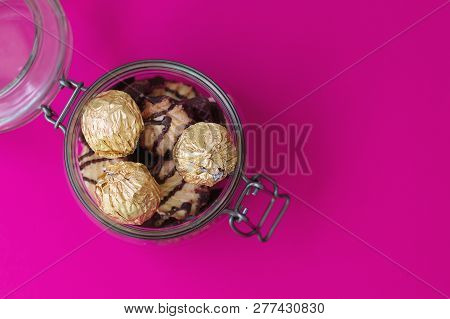 Sweets In Foil And Cookies In A Glass Jar On Pink Background. Jar With Sweets, Top View