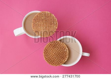 Dutch Caramel Waffles On Top Of Cup With Coffee, Pink Background. Stroopwafel. Two Coffee Mugs And P