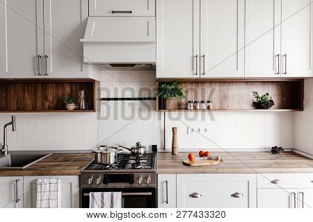 Cooking Food On Modern Kitchen With Furniture In Grey Color And Wooden Tabletop.  Knife On Wooden Cu