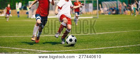 Junior Soccer Match. Football Game For Youth Players. Boys Playing Soccer Match On Football Pitch. F