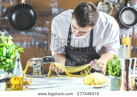 Chef Making Spaghetti Noodles With Pasta Machine On Kitchen Table With Some Ingredients Around