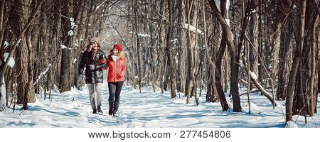 Couple having a winter walk on a chilly cold day in the woods down a path in the snow