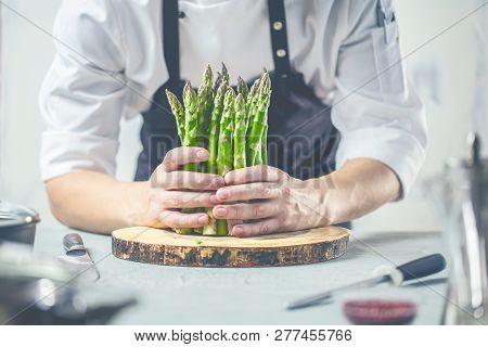 Green Asparagus Kept In Men's Chef Cook Hands.