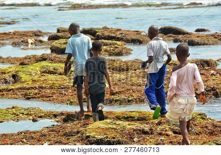 African Children Walk On Ocean Shore. Developing Countries Of Africa. Ghana, Accra - January 29, 201