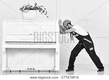 Man with beard worker in helmet and overalls pushes, efforts to move piano, white background. Heavy loads concept. Courier delivers furniture, move out, relocation. Loader moves piano instrument poster
