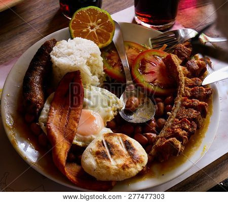 Bandeja Paisa Tipical Food Of The Region Of Antioquia Colombia with Beans Sausage Eggs Pork Plantain