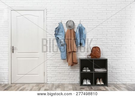 Stylish Hallway Interior With Door, Shoe Rack And Clothes Hanging On Brick Wall