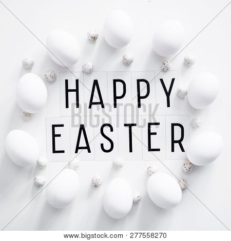 Flat Lay Close Up Of Happy Easter Greetings And Eggs Over White Background