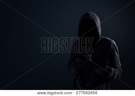 Hooded Computer Hacker With Obscured Face Using Digital Tablet In Cybercrime And Cybersecurity Conce