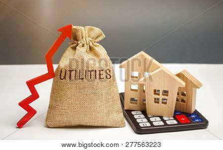Money Bag With The Word Utilities And An Up Arrow And Houses On A Calculator. The Concept Of Raising