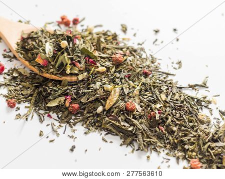 Dry leaves of Sencha green flower tea with cowberry leaf, red currant, Jasmine, rose petals, honey granules, forest berry aroma on white background poster