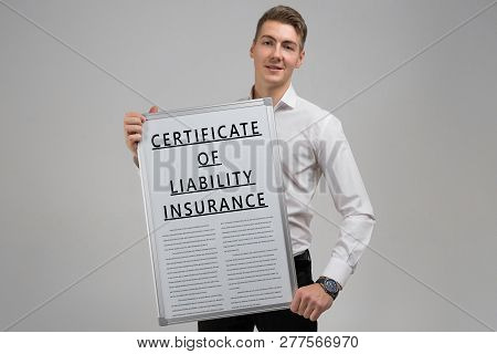 Young Man Holding A Certificate Of Liability Insurance Isolated On A Light Background