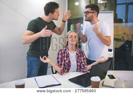 Picture Of Tow Oyung Men Having Argue. They Wave With Hands And Scream. Young Blonde Woman Sit Comfo
