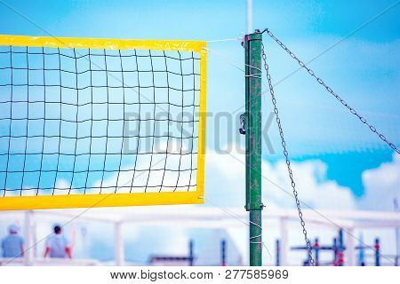 Beach Volleyball. Game Ball Under Sunlight And Blue Sky. Volleyball Net On The Tropical Beach