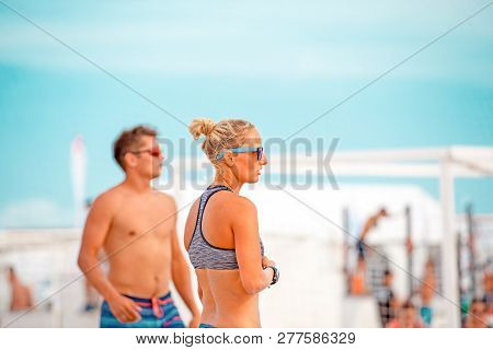 Beach Volleyball. Game Ball Under Sunlight And Blue Sky. Group Of Volleyball Beach Players Getting R