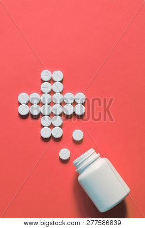 White Pills Laid Out In The Shape Of A Cross. White Pills Scattered On A Pink Background. Pills Spil