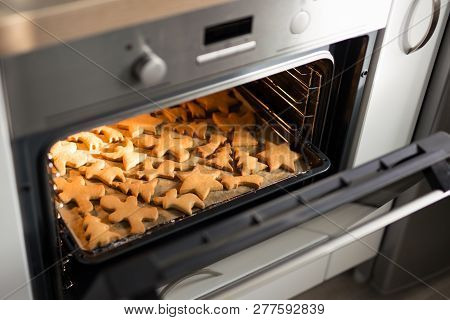 Winter Concept - Cookies Or Gingerbreads In Modern Oven In Bright Kitchen