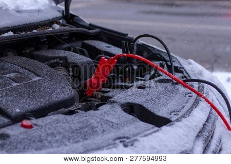 Quickly Charge The Car Battery With Jumper Cables And Another Car. Open Car Hood With Battery Wires
