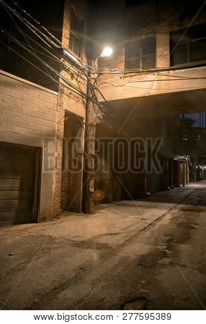 Dark and scary downtown urban city street alley scene with an eerie vintage industrial warehouse factory skyway at night in Chicago poster