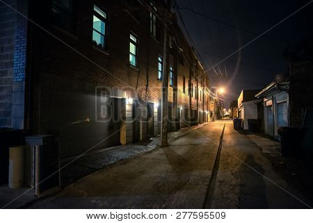 Shadow of a person in a dark scary alley at night