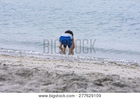 A Little Boy Playing On The Beach With Sands