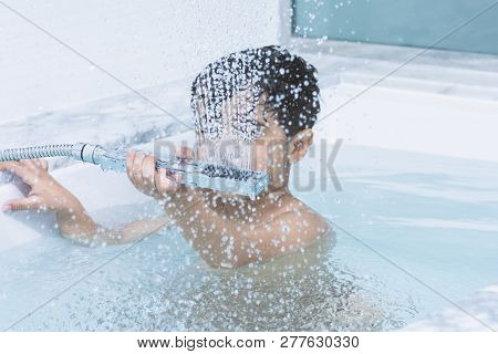 A Little Boy Take His Shower On The Bathtub Water