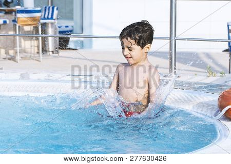 Little Boy In The Pool At Sunny Day - With Splash Water