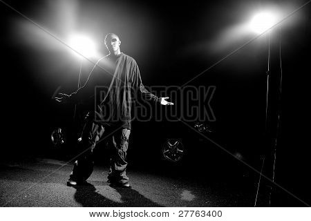 African American young man wearing baggy clothing posing under dramatic lighting with lens flare. poster