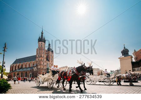 Krakow, Poland - August 28, 2018: Two Horses In Old-fashioned Coach Carriage At Old Town Square In S