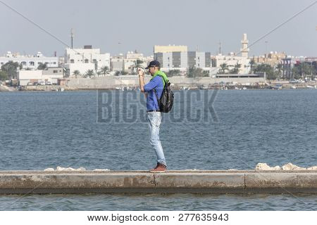 Manama, Bahrain December 29, 2018, View From Bahrain Museum, A. Man Catch His Phone And Standing Up
