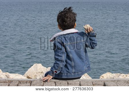 Back Of Little Boy Throwing The Stone Into The Sea
