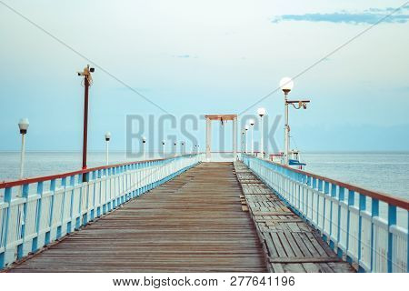 Travel. Pier On The Sea. Pier Leading To The Shore With Palm Trees.