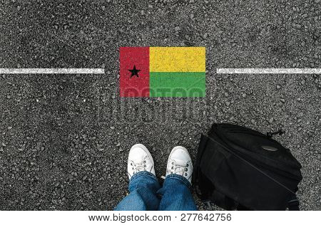 A Man With A Shoes And Backpack Is Standing On Asphalt Next To Flag Of Guinea-bissau And Border